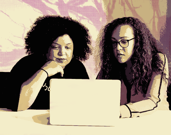 two woman using a computer together