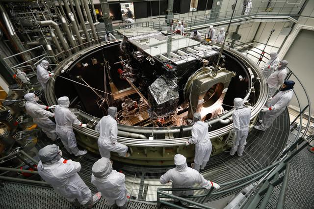 Many humans in white clean suits looking down into cylindrical chamber with GOES-S satellite inside