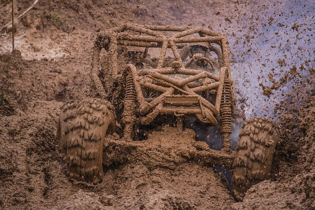 off-rod vehicle completely covered in mud and spraying mud from spinning tires
