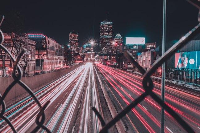 streaks of car lights seen through a broken chainlink fence